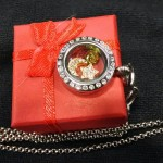 Petite silver finish locket with gold finsh moon and star paired with red and green floating charm gems