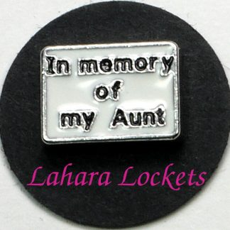 "This floating charm is a white rectangle that says ""in memory of my Aunt"" in black letters."