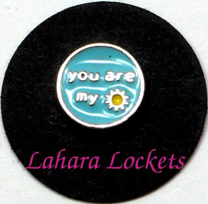 """This circular floating charm says """"you are my sunshine"""" in siver letters and has a yellow sun on a light blue background."""